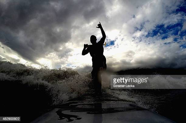 Leif Ramos signals with his hand as he catches and rides the Bore Tide at Turnagain Arm on July 13 2014 in Anchorage Alaska Alaska's most famous Bore...