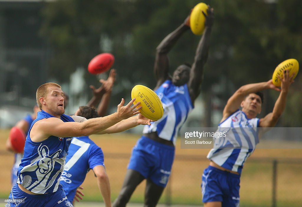 Leigh Adams, Majak Daw and Robin Nahas catch the ball during a North Melbourne Kangaroos AFL training session at Aegis Park on February 12, 2014 in Melbourne, Australia.