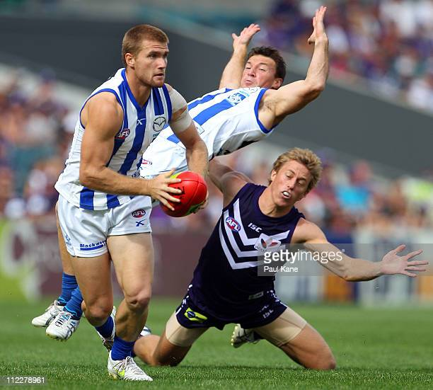 Leigh Adams of the Kangaroos looks to pass the ball after Jay van Berlo of the Dockers tackled Brent Harvey during the round four AFL match between...