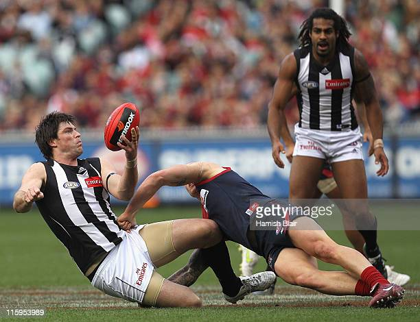 Leigh Brown of the Magpies is tackled by Nathan Jones of the Demons during the round 12 AFL match between the Melbourne Demons and the Collingwood...
