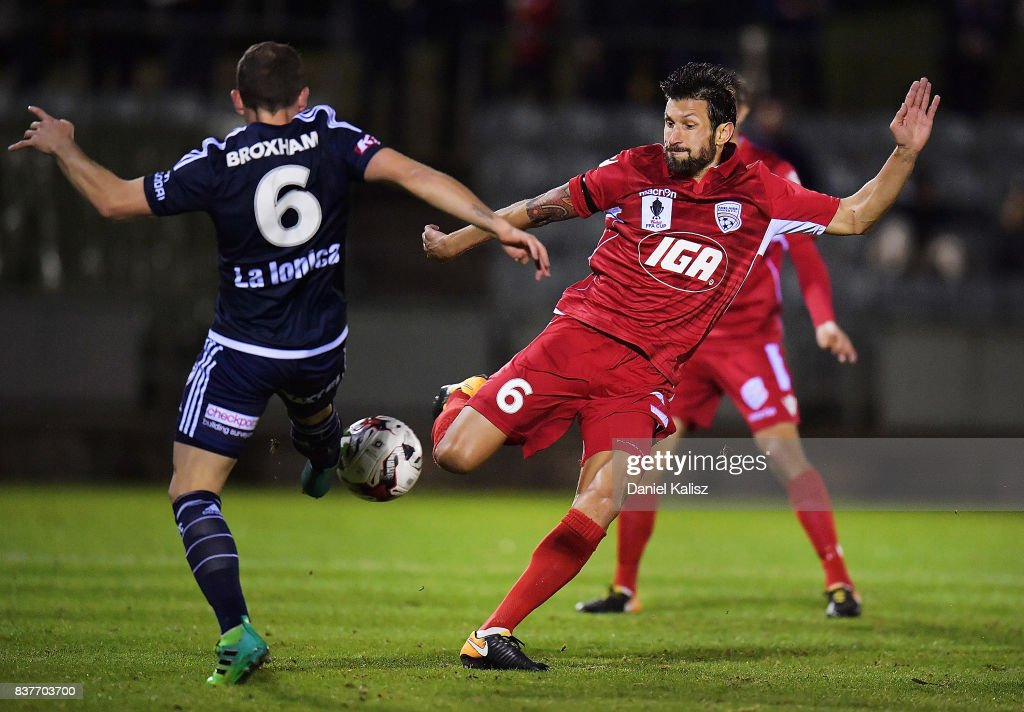 Leigh Broxham of the Victory competes for the ball with Vince Lia of United during the round of 16 FFA Cup match between Adelaide United and Melbourne Victory at Marden Sports Complex on August 23, 2017 in Adelaide, Australia.