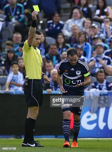 Leigh Broxham of the Victory is shown the yellow card by referee Jarred Gillett during the round eight ALeague match between Melbourne City FC and...