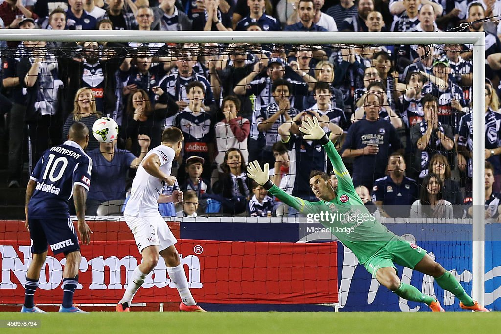 Leigh Broxham of the Victory kicks a goal past Wanderers goalkeeper Ante Covic during the round one A-League match between Melbourne Victory and the Western Sydney Wanderers at Etihad Stadium on October 10, 2014 in Melbourne, Australia.