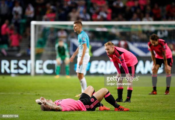 Leigh Griffiths Barry Bannan and Charlie Mulgrew of Scotland look dejected after the FIFA 2018 World Cup Qualifier match between Slovenia and...