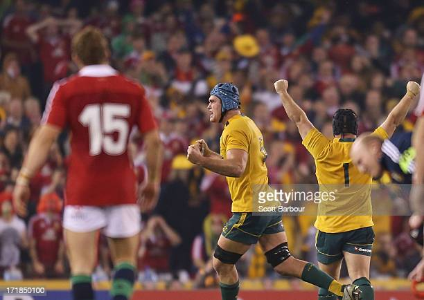 Leigh Halfpenny of the Lions looks on after attempting to kick a penalty as James Horwill and Benn Robinson celebrate victory during game two of the...
