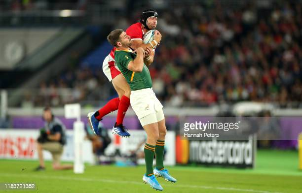 Leigh Halfpenny of Wales and Willie Le Roux of South Africa compete for a high ball during the Rugby World Cup 2019 SemiFinal match between Wales and...