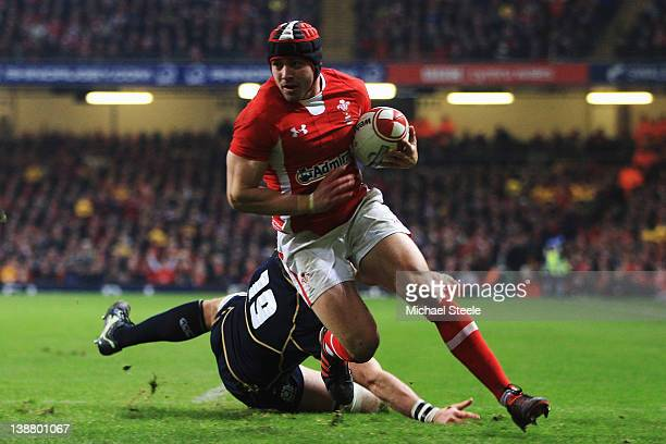 Leigh Halfpenny of Wales breaks past John Barclay of Scotland to goes over to score his second try during the RBS Six Nations match between Wales and...