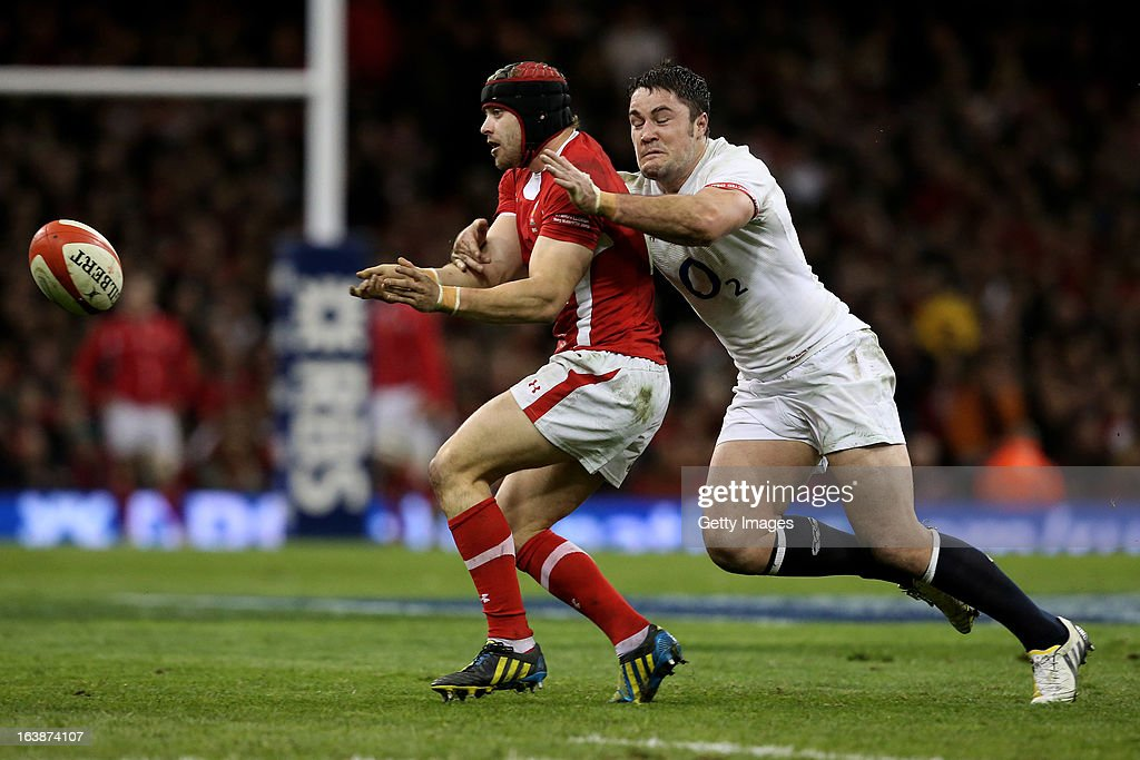 Leigh Halfpenny of Wales offloads as he is tackled by Brad Barritt of England during the RBS Six Nations match between Wales and England at Millennium Stadium on March 16, 2013 in Cardiff, Wales.