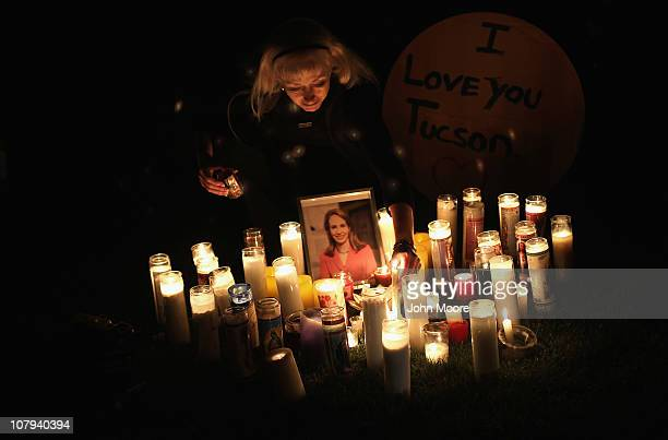 Leigh Harris adjusts candles at a vigil for US Rep Gabrielle Giffords who was shot January 8 2011 in Tuscon Arizona Giffords was shot in the head at...