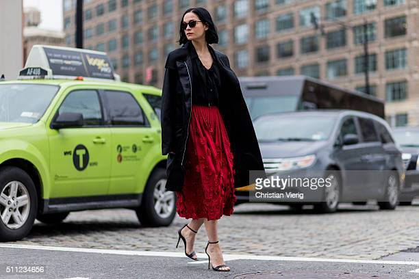 Leigh Lezark is wearing a black outdoor parka a red midi skirt with floral decoration and black strap sandals seen outside Michael Kors during New...