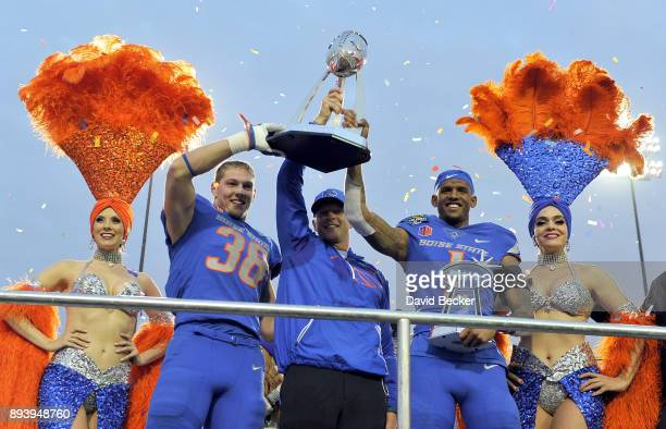Leighton Vander Esch head coach Bryan Harsin and Cedrick Wilson of the Boise State Broncos display their game winning trophy after the Broncos...