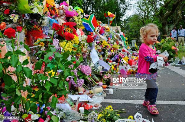 Leila de Wet two and a half years old carries flowers as she walks past a wall of flowers laid by mourners outside late South African former...
