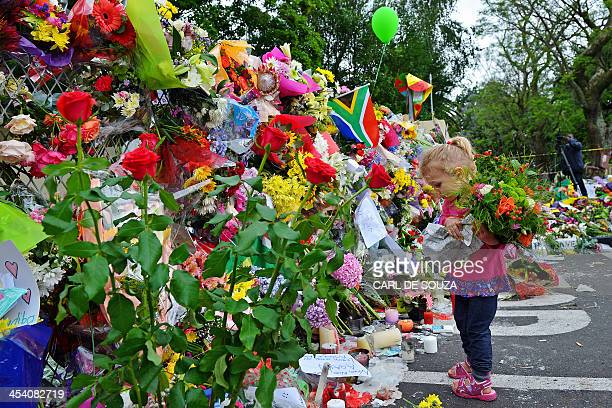 Leila de Wet two and a half years old holds flowers in front of a wall of flowers laid by mourners outside late South African former president Nelson...