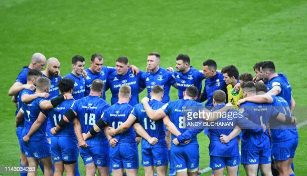 leinster players form a group huddle as they come to terms with their defeat on the field after the European Rugby Champions Cup final match between...