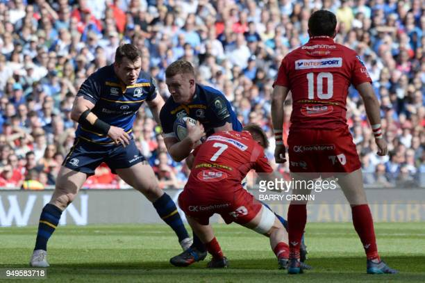 Leinster's Irish flanker Dan Leavy is tackled by Scarlets' Welsh flanker James Davies during the European Champions Cup rugby union semifinal between...