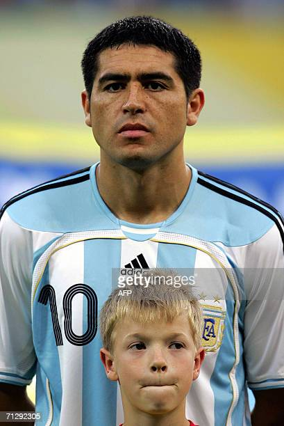 A German boy stands in front of Argentinean player Juan Roman Riquelme before the start of the World Cup 2006 round of 16 football game Argentina vs...