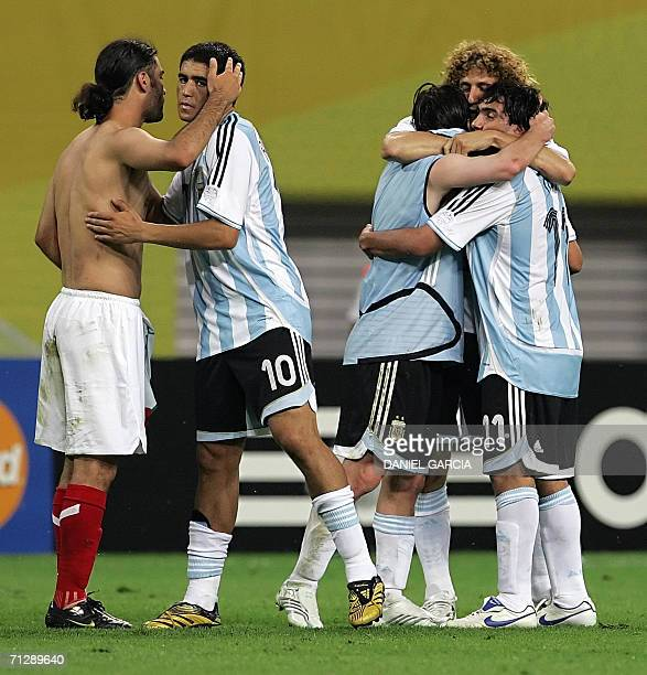 Argentinian midfielder Juan Roman Riquelme comforts Mexican defender Rafael Marquez as Argentinian players celebrate at the end of the World Cup 2006...