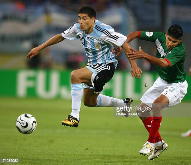 Argentinian midfielder Juan Roman Riquelme jumps as he fights for the ball with Mexican defender Carlos Salcido during the World Cup 2006 round of 16...