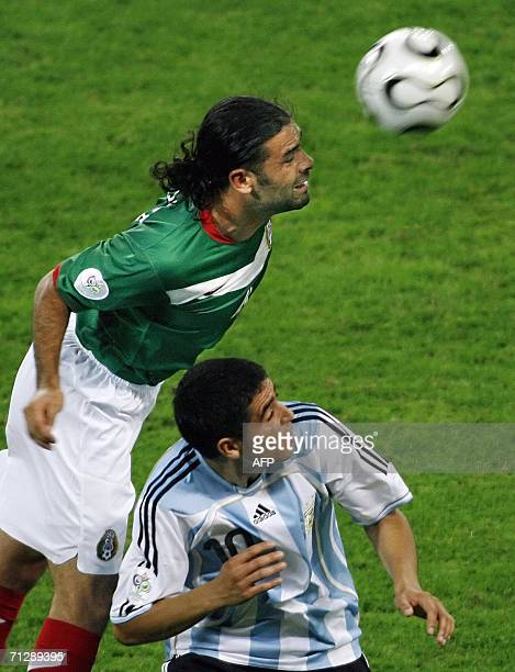 Mexican defender Rafael Marquez heads the ball next to Argentinian midfielder Juan Roman Riquelme during the World Cup 2006 round of 16 football game...
