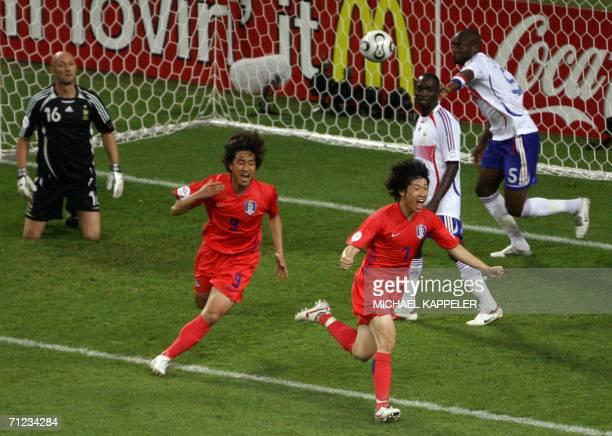 South Korean midfielder Park Ji Sung and South Korean forward Ahn Jung Hwan celebrate Park's goal against French goalkeeper Fabien Barthez while...
