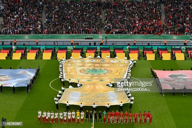 Leipzig's and Bayern Munich's teams line up during the opening ceremony of the German Cup Final football match RB Leipzig v FC Bayern Munich at the...