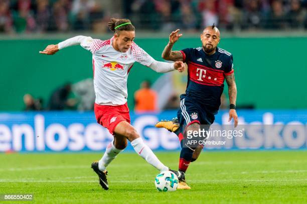 Leipzig's Danish forward Yussuf Poulsen and Munich's Chilian midfielder Arturo Vidal vie during the German football Cup DFB Pokal second round match...