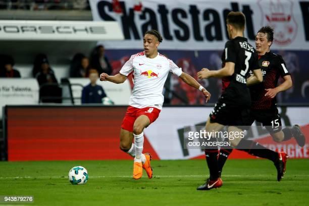 Leipzig's Danish forward Yussuf Poulsen vies with Leverkusen's Greek defender Panagiotis Retsos and Austrian midflielder Julian Baumgartlinger during...
