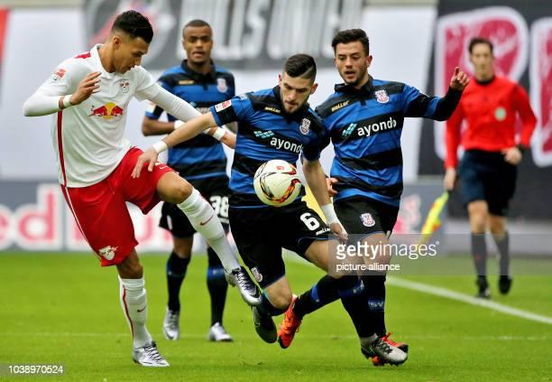 Leipzig's Davie Selke and Frankfurt's Fanol Perdedaj and Besar Halimi vie for the ball during the German Bundesliga soccer match between RB Leipzig...