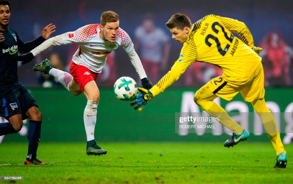 TOPSHOT - Leipzig's defender Marcel Halstenberg (C) scores against Berlin's Norwegian goalkeeper Rune Jarstein during the German first division Bundesliga football match between RB Leipzig and Hertha Berlin on December 17, 2017 in Leipzig. /