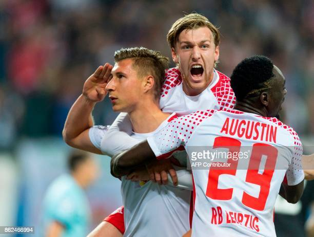 Leipzig´s defender Willi Orban celebrates scoring the opening goal with his teammate Swedish forward Emil Forsberg and French forward JeanKevin...