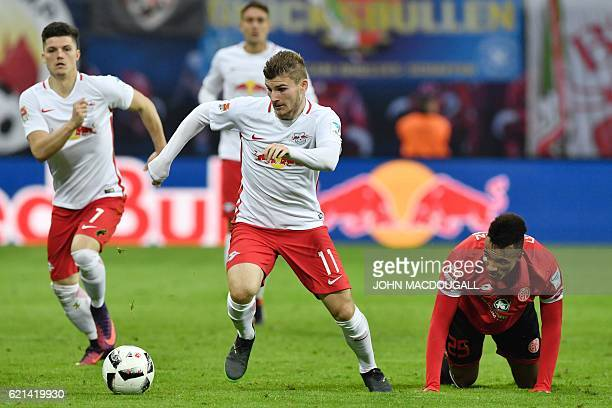 Leipzig's forward Timo Werner and Mainz' French midfielder Jean Philippe Gbamin vie for the ball during the German first division Bundesliga football...