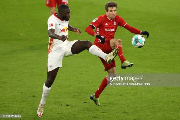Leipzig's French defender Dayot Upamecano and Bayern Munich's German forward Thomas Mueller vie for the ball during the German first division...