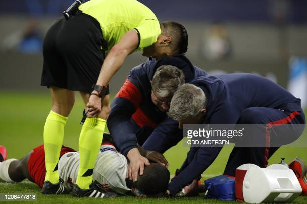 Leipzig's French defender Dayot Upamecano receives medical attention during the UEFA Champions League football match between RB Leipzig and Tottenham...