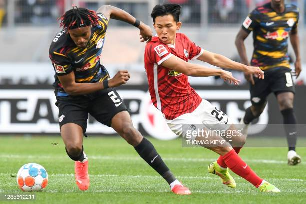 Leipzig's French defender Mohamed Simakan and Freiburg's South Korean midfielder Jeong Woo-yeong vie for the ball during the German first division...