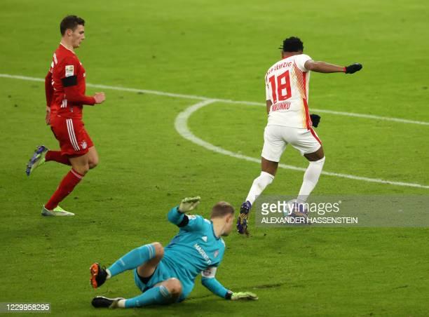 Leipzig's French midfielder Christopher Nkunku gets past Bayern Munich's German goalkeeper Manuel Neuer and Bayern Munich's French defender Benjamin...