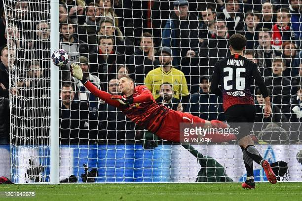 Leipzig's Hungarian goalkeeper Peter Gulacsi dives to make a save during the UEFA Champions League round of 16 first Leg football match between...