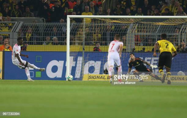 Leipzig's JeanKevin Augustin scores a penalty shot on Dortmund goalkeeper Roman Burki's goal for the 13 during the German Bundesliga soccer match...