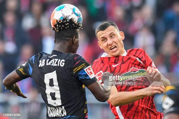 Leipzig's Malian midfielder Amadou Haidara and Freiburg's German midfielder Maximilian Eggestein both both jump to head the ball during the German...