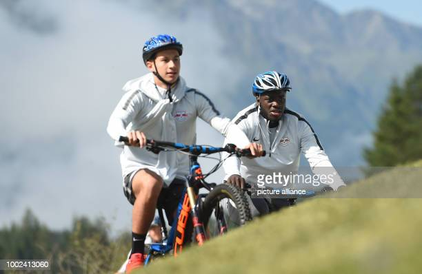 Leipzig's Nicolas Kuehn and Dayot Upamecano riding mountain bikes arrive to a training session of German Bundesliga soccer club RB Leipzig in Seefeld...