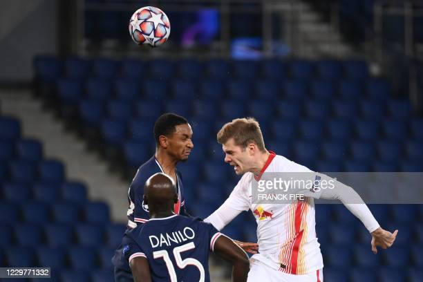 Leipzig's Norwegian forward Alexander Sorloth and Paris SaintGermain's French defender Colin Dagba jumps for the ball during the UEFA Champions...