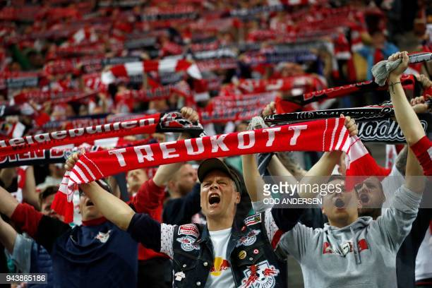 TOPSHOT Leipzig's supporters cheer up their team during the German first division Bundesliga football match between Bayer Leverkusen vs RB Leipzig in...