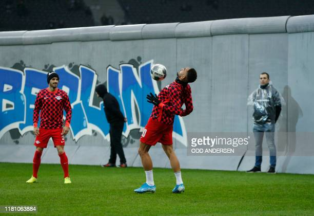 Leipzig's Uruguayan defender Marcelo Saracchi and Leipzig's Brazilian forward Matheus Cunha warm up along a mock-up of the former Berlin Wall bearing...