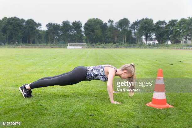 Leisure sports and personal fitness A girl keeps herself fit and makes pushups on a sports field Staged picture on August 10 2017 in Duelmen Germany