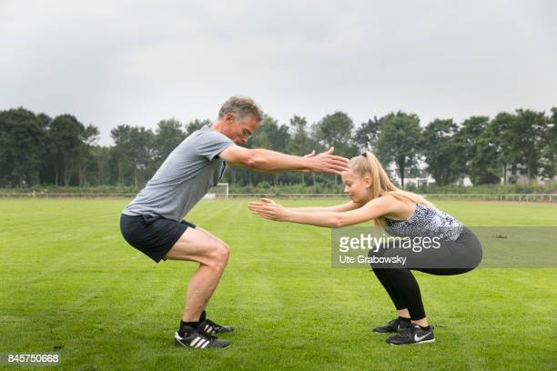 Leisure sports and personal fitness Father and daughter make squats on a sports field Staged picture on August 10 2017 in Duelmen Germany