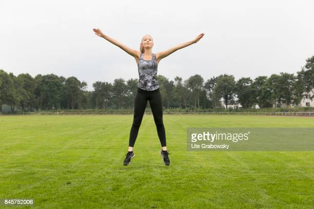 Leisure sports and personal fitness On a sports ground a young girl makes a jumping jack Staged picture on August 10 2017 in Duelmen Germany