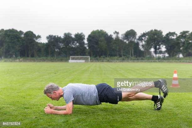 Leisure sports personal fitness A man is practicing a forearm stand on a sports field Staged picture on August 10 2017 in Duelmen Germany