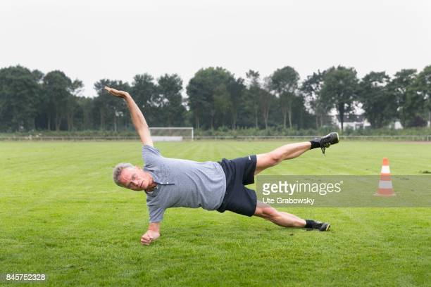 Leisure sports personal fitness A man is practicing a side plank on a sports field Staged picture on August 10 2017 in Duelmen Germany