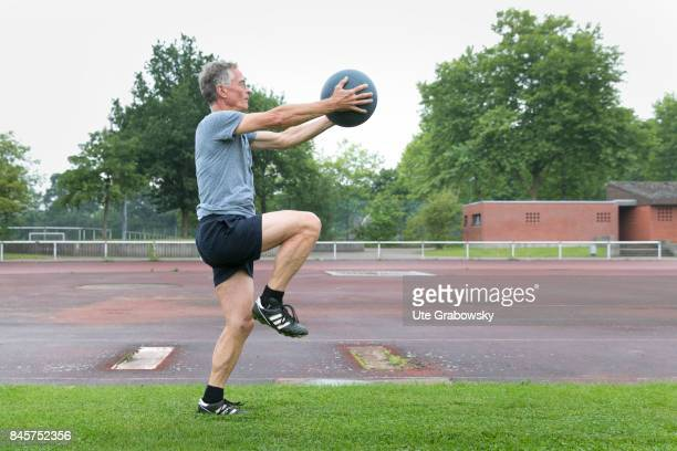Leisure sports personal fitness A man is training leg lift on a sports field In his hands he holds a medicine ball Staged picture on August 10 2017...
