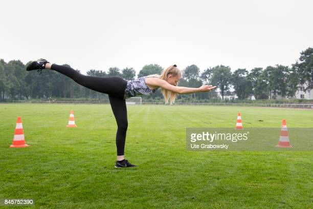 Leisure sports personal fitness A young girl exercises the airplane pose on a sports field Staged picture on August 10 2017 in Duelmen Germany