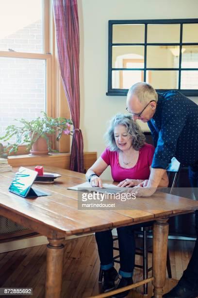 Fritid för äldre par med digital tabell och magasin.